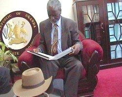 Minister for the Presidency, Mr Kirunda Kivejinja, examines the messages sent to President Museveni from Australia